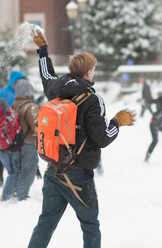 Photo of a student throwing a snowball on campus